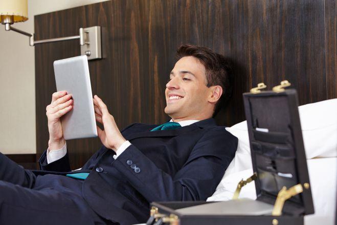 Erfolgreicher Manager liegt mit Tablet PC im Hotel auf dem Bett